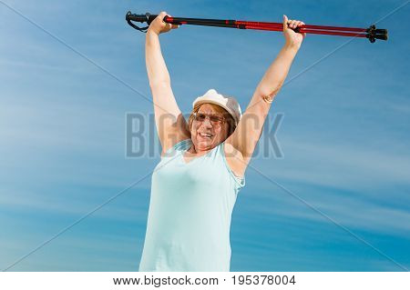 Senior woman enjoying nordic walking doing warmup exercises with poles outdoor sunny summer day. Health activity in old age.