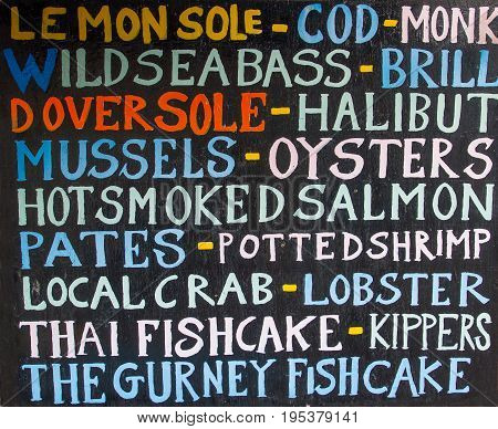 A fishmongers sign listing the fresh fish and seafood that are for sale inside his shop