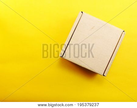 top view of paper box on yellow background