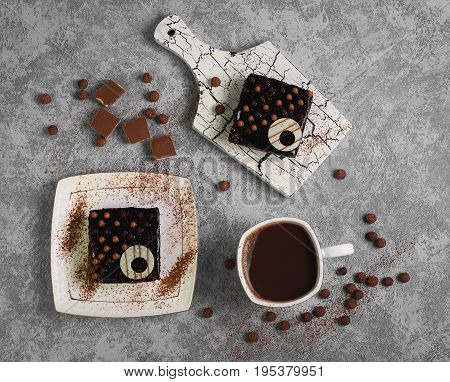 Sweet breakfast two chocolate brownies cakes and hot chocolate in  white cup. On  gray stone background the ingredients for chocolate cakes are balls and pieces of milk chocolate. Top view, flat lay