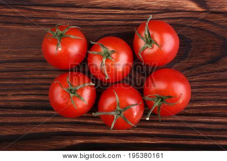 A group of tasteful red tomatoes on a brown wooden background. Veggies on a brown table. Healthful nutritious vegetables full of vitamins. Natural ingredients for tasty dinner.