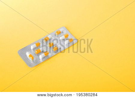 A view from above on a single package with orange and white pills on a spacious yellow background. Prescripted antibiotics in multicolored capsules close-up. Chemical therapy.