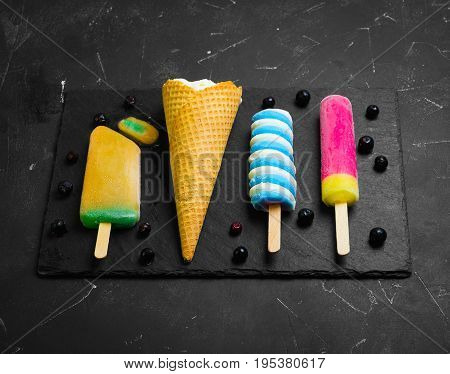 Summer ice cream assortment of fruit flavors - Ice cream in the waffle horn fruit ice. On board on dark black stone background. Ingredients for ice cream blue Frozen berries.