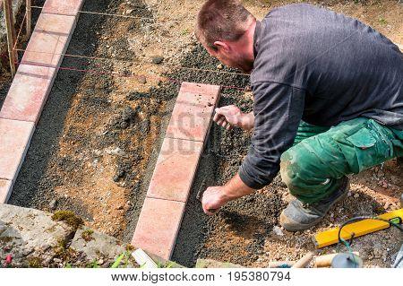 Nahaufnahme Bauarbeiter bei der Herstellung einer Maurer aus Ziegelsteinen auf der Baustelle.