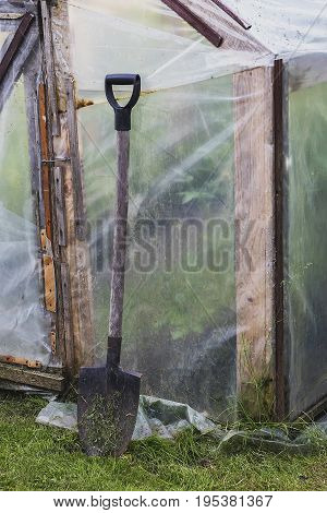 with the ground at the greenhouse door propped up filthy shovel
