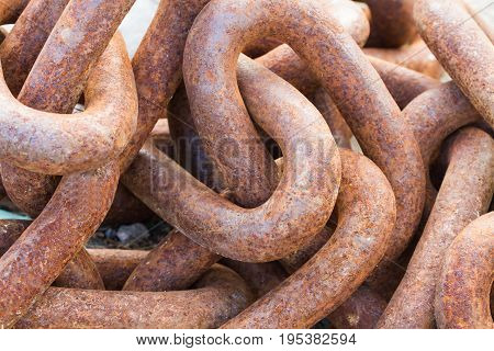 Thick and heavy industrial chains that are rusted and worn in a full frame, industry background image.