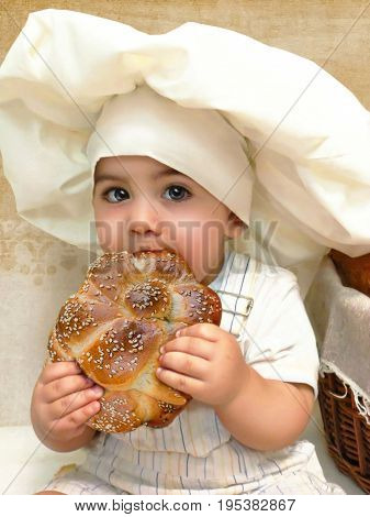 Baby dressing in a big bakers hat eats a big roll, little cook