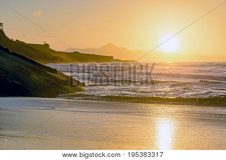 Tropical sunrise at Devil beach with Copacabana Fort in the background at Rio de Janeiro