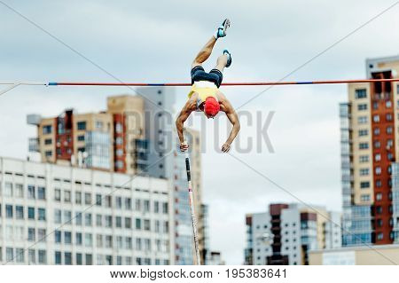 pole vaulter male athlete successful attempt over bar