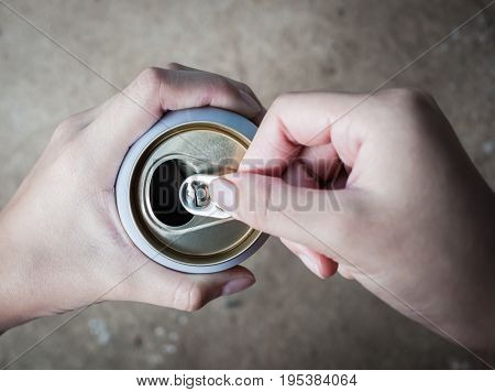 closeup hand holding and opening a can