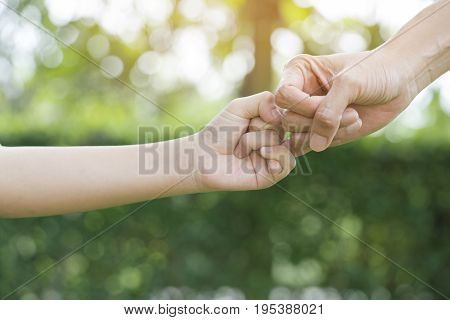 A mother and her child hooking their fingers to make a promise