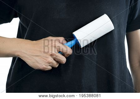 woman removing dog and cat hair from clothes using adhesive roller