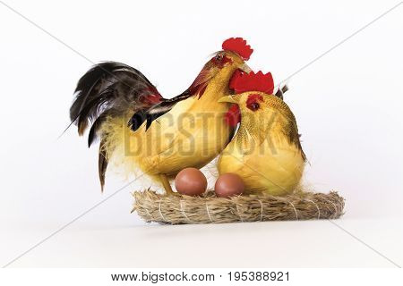 Tabletop figurine of a rooster and hen on a white background.