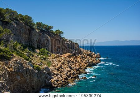 Cliffs and trees against the Mediterranean sea on a sunny day on the Costa Brava