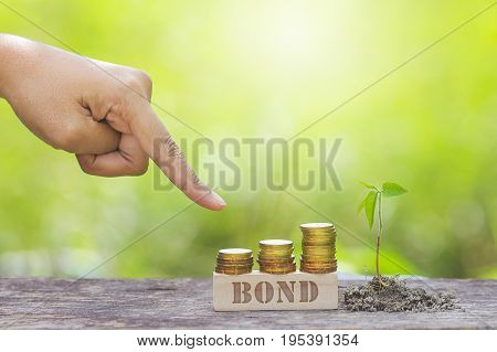 BOND WORD WITH BUSINESSMAN HAND POINTING TO STACK OF GOLD COIN