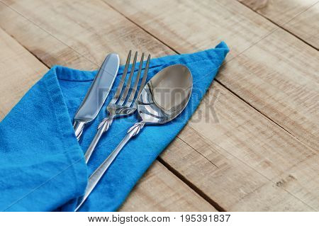 Fork knife and spoon and blue napkin on wooden table. Dining silverware