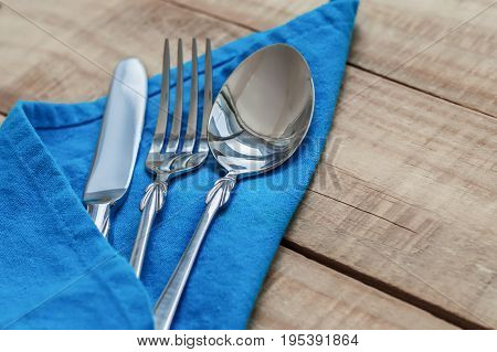 Silver tableware on blue napkin. Big spoon fork and knife with blue napkin on wooden table
