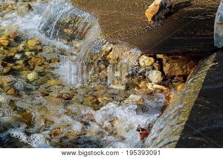 Waterfall at the source. Small Modern fountain in the park on the summer territory. A small fountain in the middle of a small artificial lake
