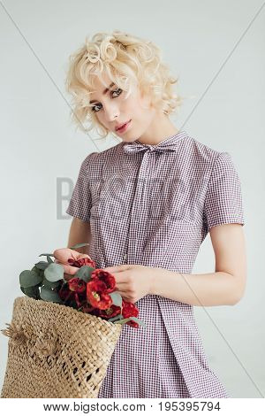 Girl with a mysterious gaze holds wicker bag with flowers