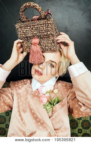 Sad girl in pink clothes holds a bag over her head