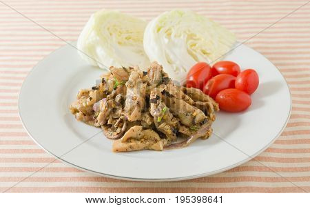 Thai Cuisine and Food Thai Traditional Nam Tok or Spicy Grilled Pork Salad Served with Cabbage and Cherry Tomatoes.