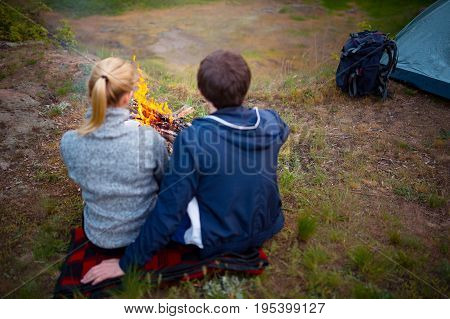 Young family of hikers resting near campfire at camp in forest camping travel tourism hike and people concept.