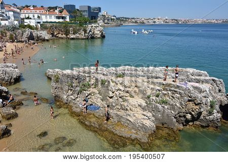 CASCAIS PORTUGAL - JUNE 07 2017: People sunbathing on the Praia da Rainha public beach. Cascais is famous and popular summer vacation spot for Portuguese and foreign tourists