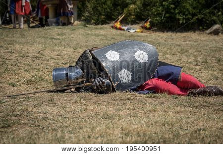 Medieval knight fallen in battle, on a reenactment with costumed characters and medieval armor with chainmail, helmet swords and shields. Medieval demonstration and recreation