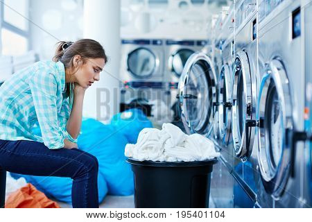 Bored Woman Sitting Opposite To Washing Machines