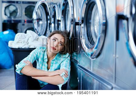Bored Woman Sitting Near Washing Machines