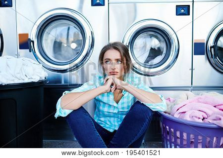 Disappointed Woman Near Washing Machines And Baskets