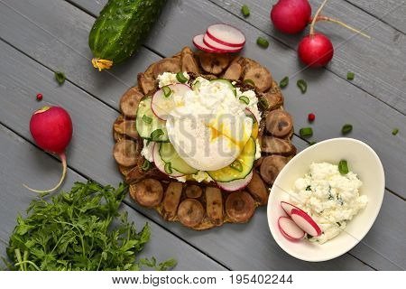 Sandwich with cream cheese radish cucumber and poached egg, top view