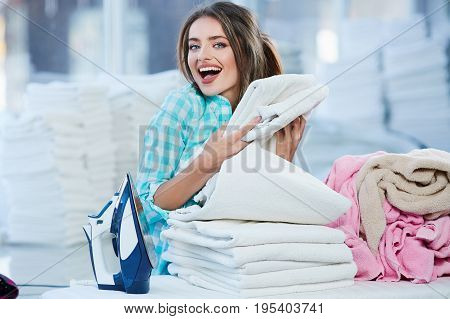 Girl Piling White Linen Into Heap