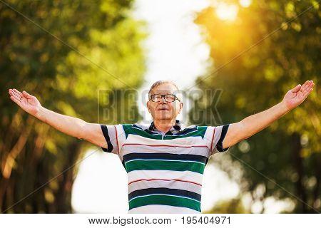 Senior man enjoys spending time in the nature.