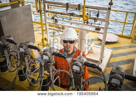 TechnicianInstrument technician on the job calibrate or function check pressure transmitters in process oil and gas platform offshoretechnician
