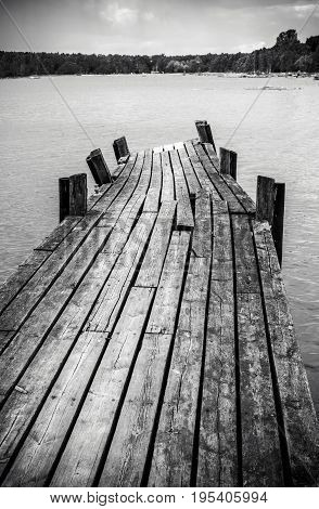 Old long and worn wooden foot bridge in water