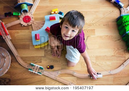 Sweet preschool child boy playing with wooden railway and trains at home top view