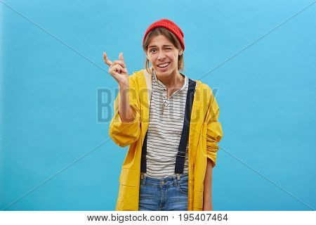 Young Attractive Woman Wearing Red Hat, Yellow Jacket And Jean Overalls Showing Something Very Littl
