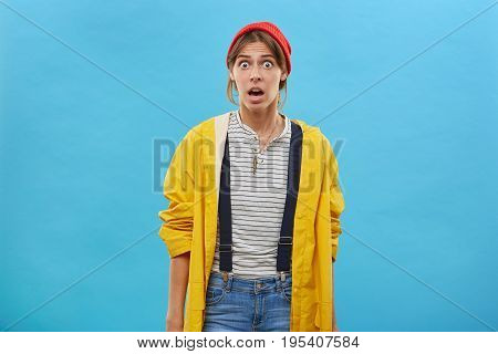 Portrait Of Shocked Woman Looking With Bugged Eyes And Opened Mouth Posing Against Blue Background R