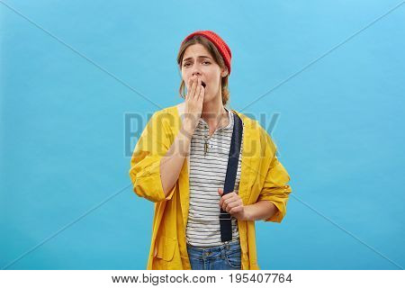 Tired Female Worker In Casual Clothes Yawning Covering Her Mouth With Hand Wanting To Sleep. Hard-wo