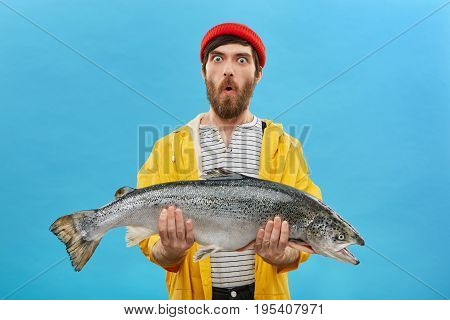 Amazement And Unexpectedness Concept. Shocked Young Fisherman With Thick Beard Looking With Bugged E