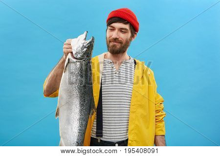 Portrait Of Glad Fisherman Wearing Red Hat, Yellow Jacket And Overalls Looking With Pleased Expressi