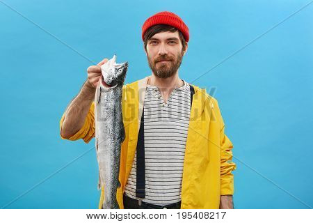 Studio Shot Of Successful Bearded Fisherman Standing Over Blue Background With His Catch Having Happ