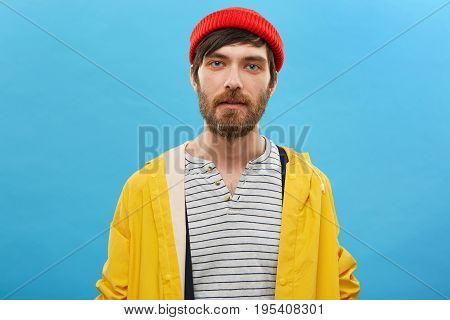 Bearded Sailor Dressed In Red Hat And Yellow Anorak Posing Against Blue Background. Serious Man With