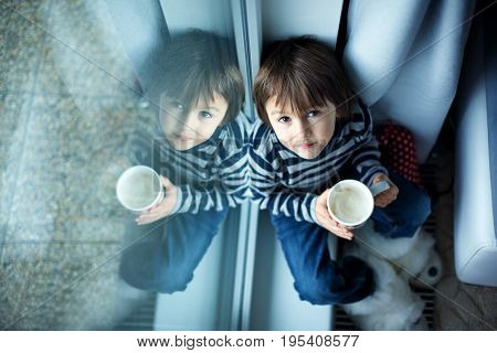 Adorable Little Preschool Child, Boy, Drinking Milk, Sitting On Window Shield