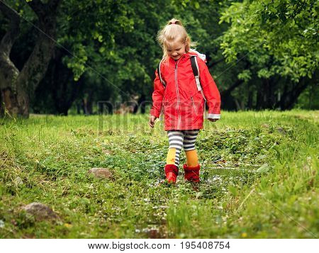 The child in bright rubber boots and a jacket . A girl walks through the puddles. Green grass trees