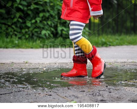 Child's feet in rubber boots. Girl standing in a puddle. Green grass trees