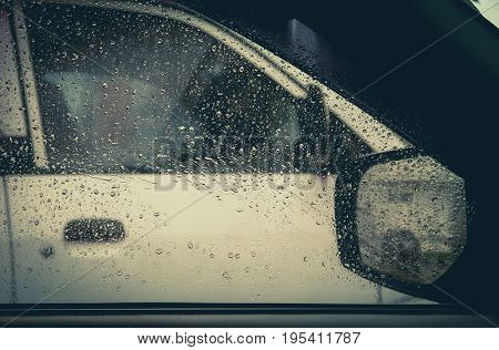 Water drop on glass mirror of car with white car.