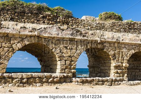 The waves of the Mediterranean sea visible through the ruined arches of the ancient aqueduct in Caesarea. Israel.