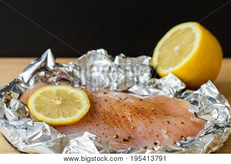 Uncooked chicken fillet in foil paper with lemon salt and black pepper. Raw chicken breast. Healthy cooking